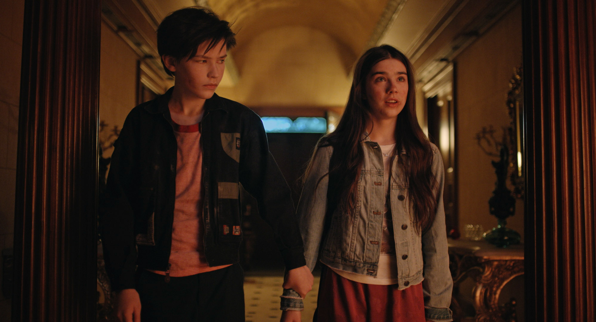 Jacob and Isabel stand together in a hall lit with red-orange light. He is looking at her and holding onto her wrist, while she looks ahead with a shocked/scared expression.
