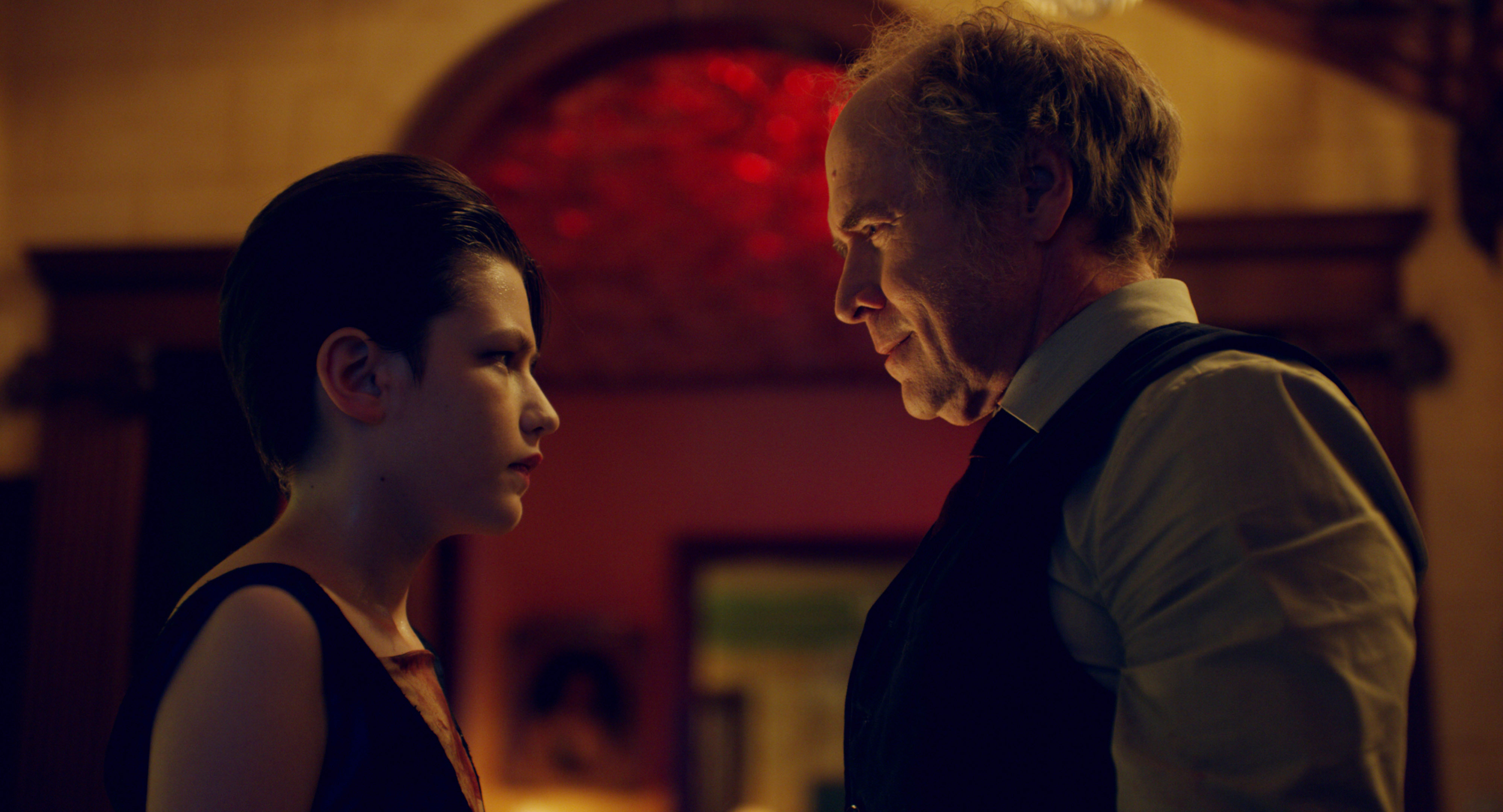 Jacob and Dr. Sherman face each other in a red-lit room.