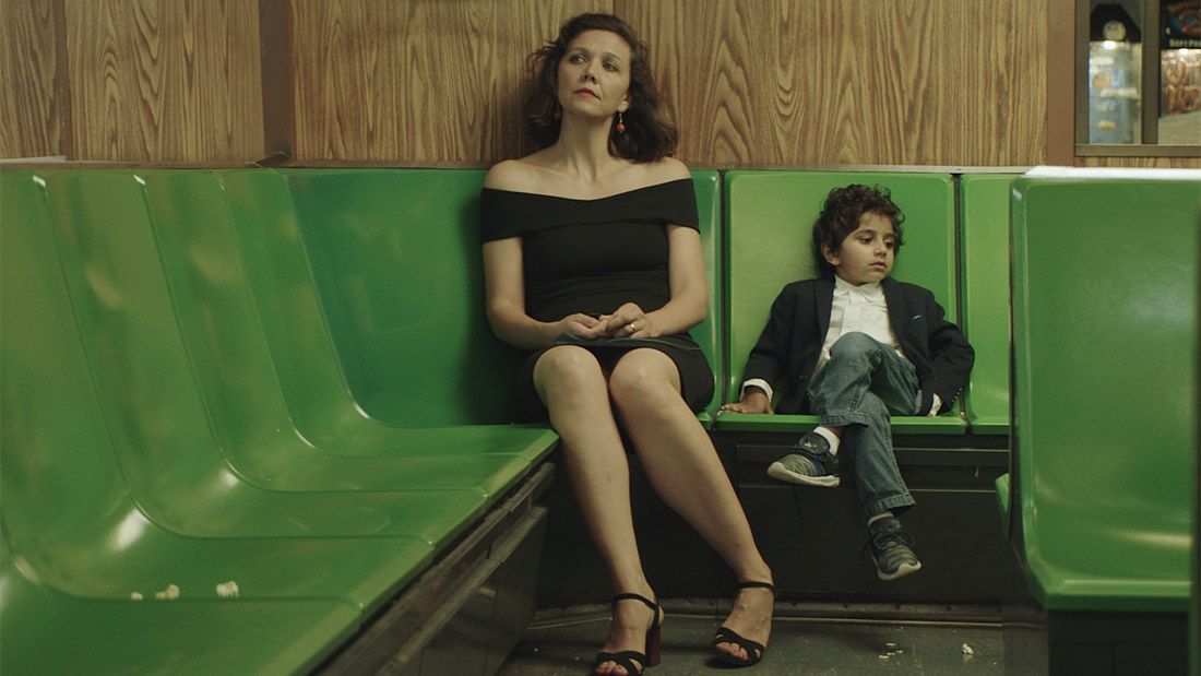 Promotional photo for The Kindergarten Teacher, with Maggie Gyllenhaal wearing a black dress looking into the distance to the left and a small child sitting next to her with his legs crossed, looking in the opposite direction. The chairs are green plastic and the walls are a medium-tone wood with prominent grain.